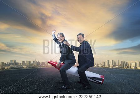 Two Senior Business Man Riding On Children Rocket Toy Standing On Asphalt Ground With Urban Scene Ba