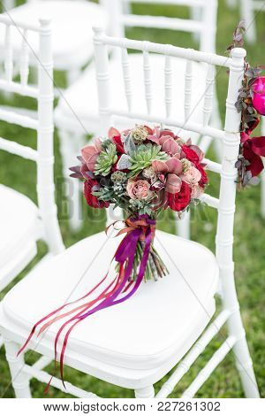 Stunning Red Bridal Bouquet On White Chair. Wedding Ceremony. Mix Of Succulents, Orchids And Roses.