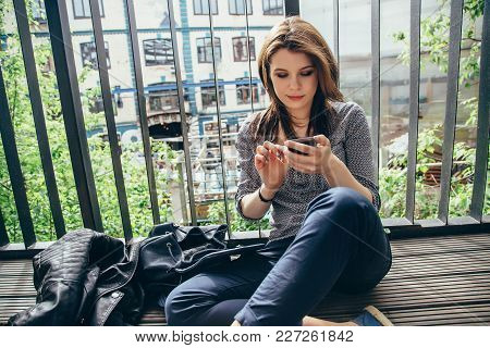 Young Girl Using A Smartphone On A Balcony