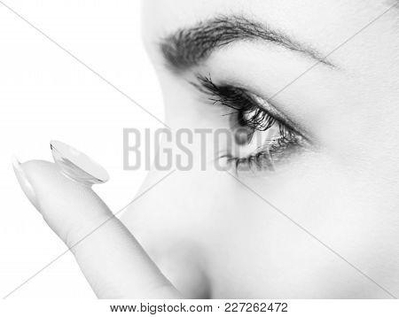 Close-up Shot Of Young Woman Wearing Contact Lens For A Better View. Over White Background.