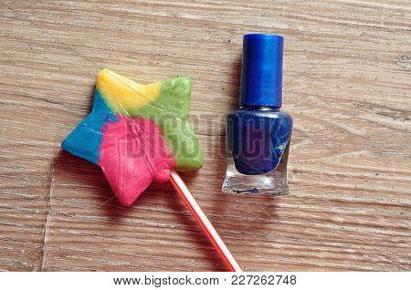 A Bottle Of Blue Nail Polish With A Colorful Star Shape Lollipop
