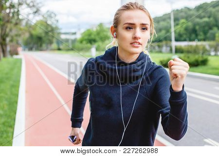 Young Beautiful Woman Running Outdoors. The Concept Of Sport And Active Lifestyle.