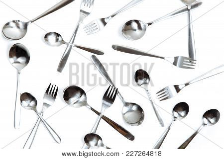 Many Cutlery Spoons And Forks On A White Isolate.