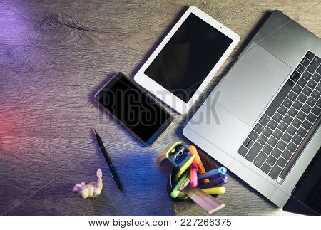 Laptop, Smart Phone, Tablet Pc And Power Bank On Dark Wooden Background In The Office. Top View