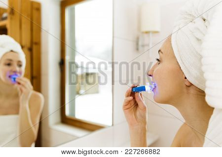 Woman Is Whitening Teeth With Special Toothpaste And Led Light At Home. Beauty Concept