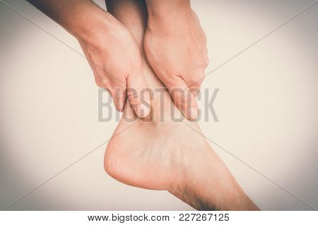 Woman With Ankle Pain Holding Her Aching Leg - Body Pain Concept - Retro Style
