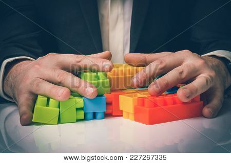Concept Of Strategy And Reorganization Business Ideas - Young Businessman Playing With Colored Toy B