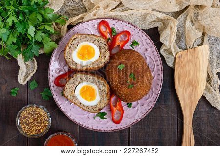 Large Juicy Cutlets Stuffed With Boiled Egg On A Dark Wooden Background. Scottish Cutlet. The Top Vi