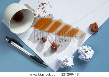 Conceptual Photo With Spilled Coffee, Crumpled Paper, Cookie Crumbs And A Pen On Blue Desk. Top View