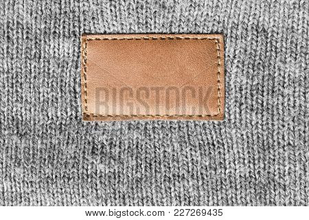 Blank Brown Leather Clothes Label On Grey Knitted Background