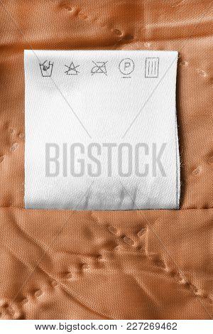Care Clothes Label On Textile Orange Background Closeup