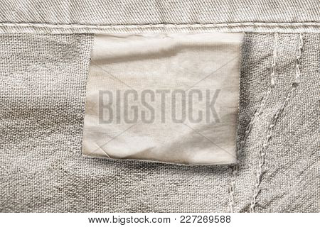Blank Clothes Label On Beige Cotton Background Closeup