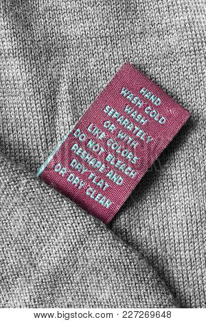 Textile Care Clothes Label On Grey Knitted Wool Background
