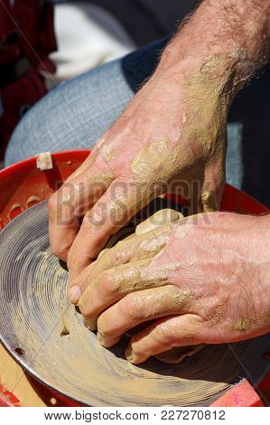 Hands Of Master Creating Clay Jar With Potter Wheel. Master Makes Earthenware Jug