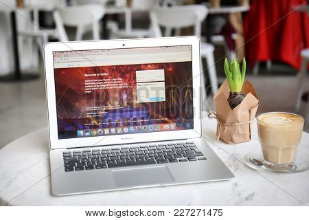 KYIV, UKRAINE - JANUARY 15, 2018: Modern Apple Macbook Air displaying Twitter homepage on screen at table