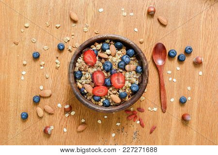 Granola Bowl With Fresh Strawberries And Blueberries On Wooden Table. Flat Lay, Concept Of Healthy L