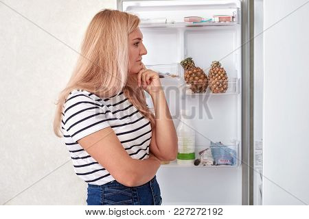 Woman Is Standing In Front Of The Fridge And Thinks What To Eat.
