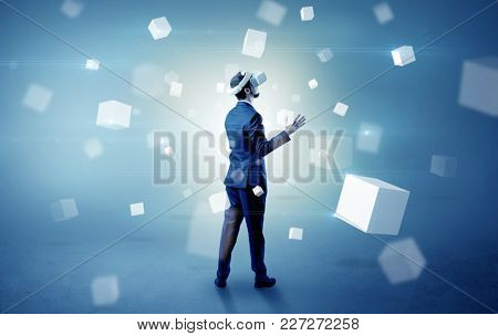 Handsome businessman with vr goggle and falling white cubes around