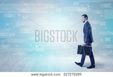 Handsome businessman walking in suit with briefcase on his hand and online communication concept around