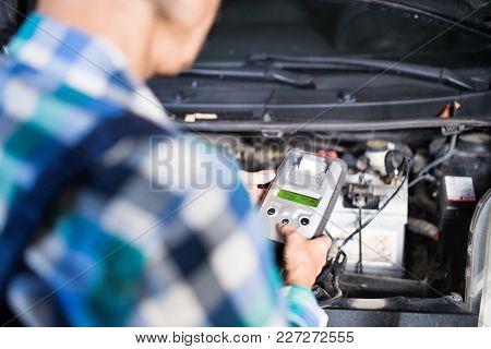 Unrecognizable Female Mechanic Repairing A Car. A Senior Woman Working In A Garage.