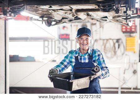 Female Mechanic Repairing A Car. A Senior Woman Working In A Garage.