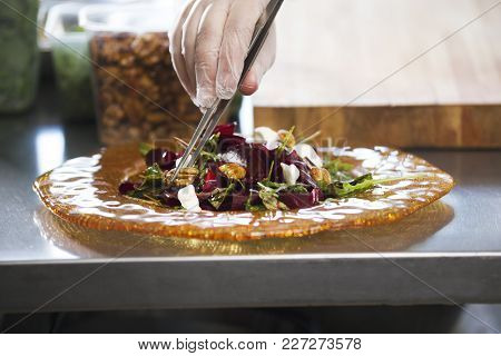 Chef Preparing And Serving A Salad In The Kitchen Of The Restaurant, Concept Of Cooking And Haute Cu