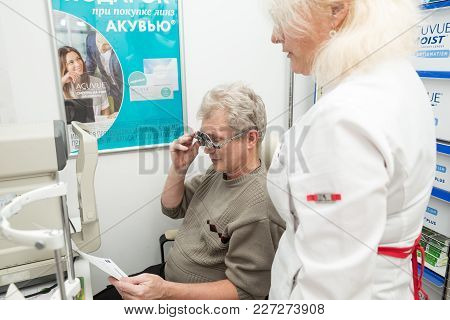 SAINT PETERSBURG, RUSSIA - FEBRUARY 13, 2018: A woman optometrist checks vision for a mature man. Doctor and patient with model releases