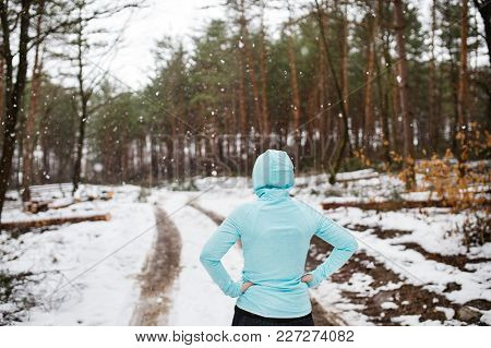 Senior Woman Jogging Outside In Winter Nature, Resting. Rear View.