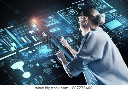 Looking Interested. Clever Experienced Young Programmer Standing In Front Of A Big Futuristic Device