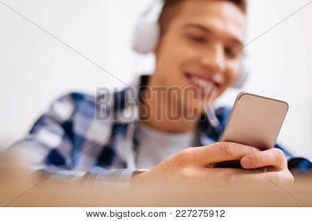 Relaxing. Attractive Exuberant Fair-haired Boy Smiling And Wearing Headphones And Listening To Music