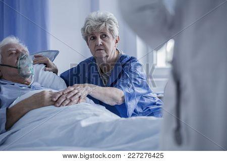 Elderly Woman Supporting Sick Man
