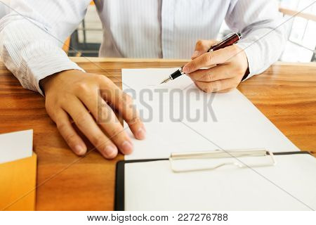 Close-up Of Businessperson Signing Contract,woman Writing Paper At The Desk With Pen And Reading Boo