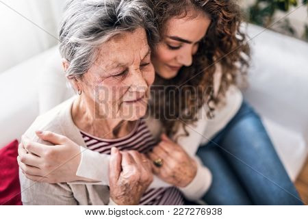 A Teenage Girl With Grandmother At Home, Hugging. Family And Generations Concept.