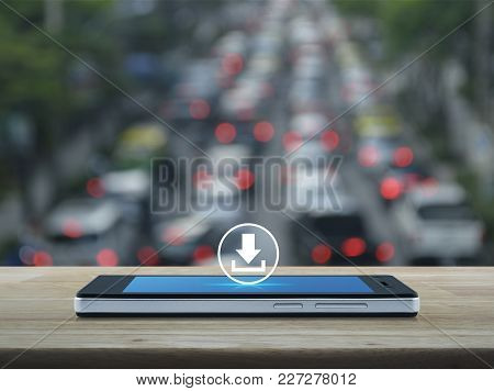 Download Icon On Modern Smart Phone Screen On Wooden Table Over Blur Of Rush Hour With Cars And Road