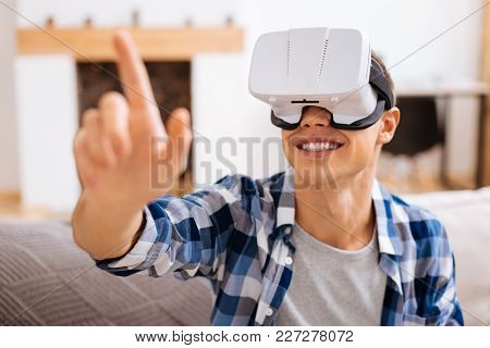 Amusing. Inspired Well-built Stylish Adolescent Wearing A Vr Headset And Relaxing And Touching The I
