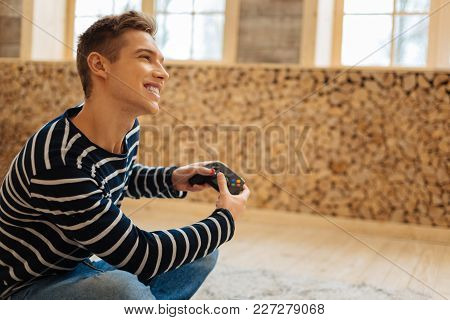 My Favourite Game. Good-looking Exuberant Fair-haired Young Man Smiling And Holding A Remote Control