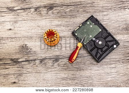 Hard Disk And A Red Screwdriver With Bits Lays On Wooden Board