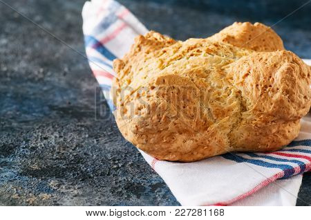 Traditional Irish Soda Bread On A Towel On A Blue Stone Background.