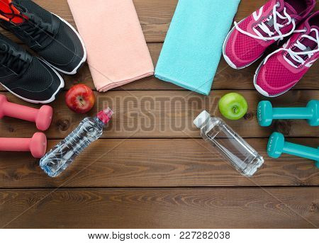 Double And Opposite Fitness Concept With Sneakers Dumbbells Bottle Of Water And Apple On Wooden Tabl