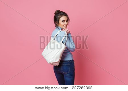 Cheerful Casual Young Woman With Bag Looking At Camera On Pink Background.