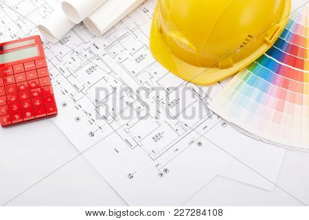 Architectural blueprints, safety helmet, color guide on a white background. Architect workplace. Engineering tools. Top view.