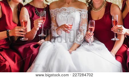 Bride And Happy Girlfriends With Glasses Of Wine In Their Hands Clink And Celebrate At The Wedding P