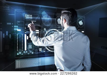 Changing Settings. Qualified Calm Programmer Standing In His Office In Front Of A Transparent Screen