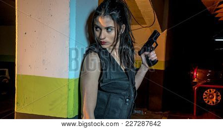 Killer, armed and dangerous girl in a parking lot, wearing a black leather jacket and a bulletproof vest