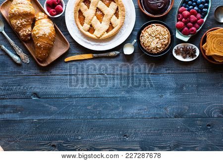 Top view of a wood table full of cakes, fruits, coffee, biscuits, spices and more breakfast classic sweet foods.