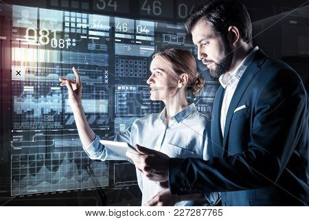 Team Work. Optimistic Smart Woman Pointing To The Screen Of A Futuristic Computer While Her Attentiv