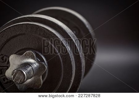 exercise concept - iron dumbbell on a black background, black and white image