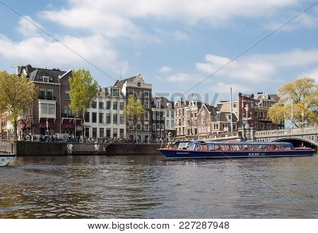 Amsterdam, Netherlands - April 20, 2017: Canal  Scene With A Tour Boat, Bridges, Streets And Traditi