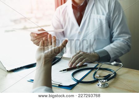 Male Doctor Handing A Prescription To The Patient.