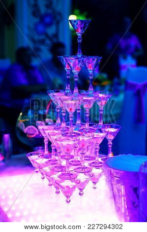 Tower Of Martini Glasses In The Restaurant With Ultraviolet Illumination